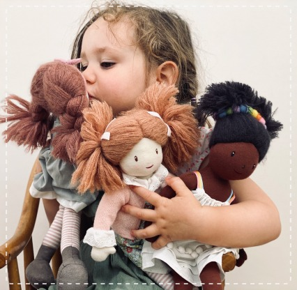 Little girl holding an armful of her favourite rag dolls and soft toys.