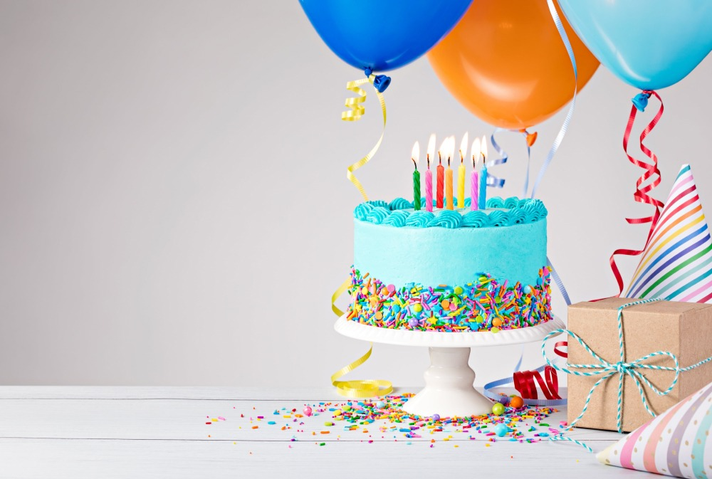 Birthday cake with candles and balloons, with gift wrapped toys for children
