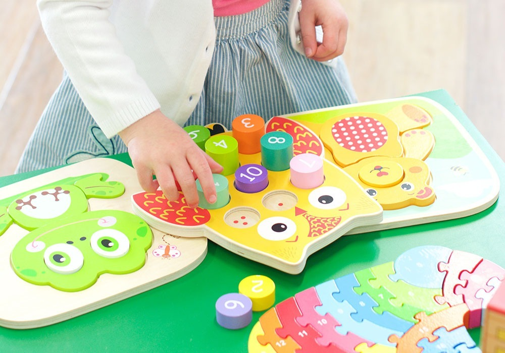 Little girl playing with number puzzle. Toys and puzzles for young children